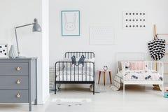 Lampe sur le coffret gris dans l'intérieur lumineux de chambre à coucher d'enfants avec le bl photos libres de droits