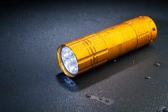 Lampe-torche de la poche LED sous la pluie sur une surface foncée Baisses de l'eau Photos stock