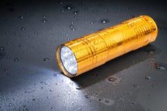 Lampe-torche de la poche LED sous la pluie sur une surface foncée Baisses de l'eau Image libre de droits