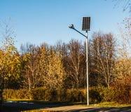 Lampe-torche sur les batteries solaires en parc d'automne Images libres de droits