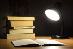 Lampe und Bücher in der Dunkelheit stockfoto