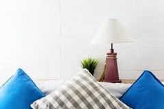 Lampe und Grünpflanze auf Kopfende mit den blauen und grauen pollows Hotelzimmerinnenhintergrund stockbild