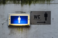 Lampe und Signage mit dem Zeichen der Raumtoilette der Männer auf einem alten Stockfotos