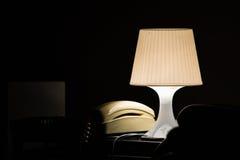 Lampe und Telefon in einem dunklen Hotelzimmer Stockbild