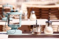 Lampe, Zucker und Salz auf dem Tisch eines Sommercafés Lizenzfreies Stockbild