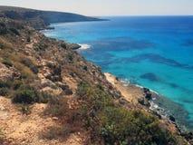 Lampedusa en Italie avec la falaise et nettoient la mer bleue images stock
