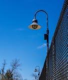 Lampen auf Maschendrahtzaun Stockfoto
