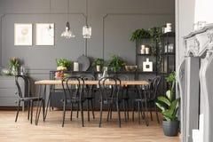 Lampen boven houten lijst en zwarte stoelen in grijze eetkamer binnen stock afbeeldingen