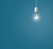 Lampen, die von oben genanntem auf einem blauen Hintergrund hängen Stockfotografie