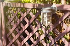 Lampen für Beleuchtung auf einem Bretterzaun im Garten Stockfoto