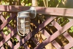 Lampen für Beleuchtung auf einem Bretterzaun im Garten Lizenzfreie Stockfotos