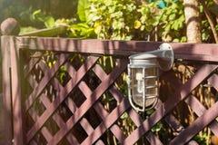 Lampen für Beleuchtung auf einem Bretterzaun im Garten Stockbild