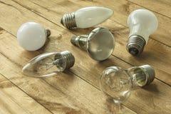 Lampen mit unterschiedlicher Kappe liegen auf einer Holzoberfläche Stockbild