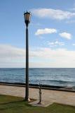 Lampenpfosten durch Ozean Lizenzfreie Stockfotografie