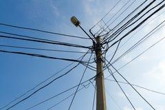 Lampenpol und Kreuz der verwirrten elektrischen Drähte Stockbilder