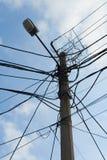 Lampenpol und Kreuz der verwirrten elektrischen Drähte Lizenzfreie Stockfotografie