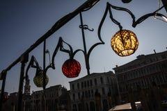 Lampes colorées sur une balustrade fleurie à Venise, Italie, avec les maisons vénitiennes à l'arrière-plan Photo stock