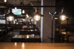 Lampes de vintage au-dessus d'une table en bois dans une barre 2 Image stock