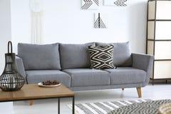 Lampion na stołowej pobliskiej popielatej kanapie z wzorzystą poduszką w bielu obrazy royalty free