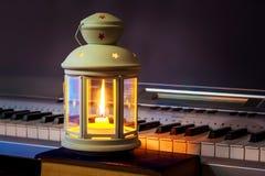 Lampion z świeczką iluminuje klucze pianino Muzyka w intymnym setting_ obrazy royalty free