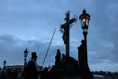 Lamplighter lights a street gas light at the Charles Bridge in P Royalty Free Stock Images