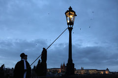 Lamplighter lights a street gas light at the Charles Bridge in P Royalty Free Stock Photography