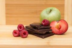 Lamponi con cioccolato fondente, Plum And Apple On Table Immagine Stock