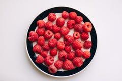 Lamponi deliziosi su un piatto con fondo bianco Fotografia Stock