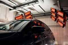 Lampor för att torka den keramiska beläggningen är bak bilen Arkivfoto