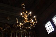 Lampor i form av stearinljus tänder på ljuskronan i forntida träortodox kyrka Arkivfoto