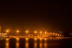Lampor på bron vid floden. Royaltyfri Foto