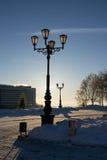 Lampost med snö och solen i bakgrund Fotografering för Bildbyråer