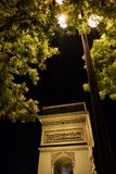 Lampost in trees at night with Arc de Triomphe lit Paris, France royalty free stock photos