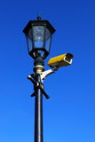 Lamppost. With cctv camera against blue sky Stock Images