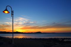 Lamppost azul alaranjado da luz do seascape do por do sol Fotos de Stock