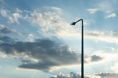 Lamppost on the background of the evening sky with the rays of the setting sun. Copy paste stock image