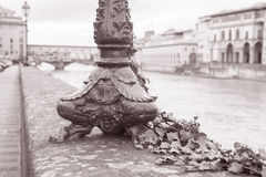 Lamppost Base and the Ponte Vecchio Bridge with River Arno, Flor Royalty Free Stock Photo