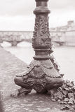Lamppost Base and the Ponte Vecchio Bridge with River Arno, Flor Royalty Free Stock Photography