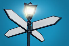 Lamppost with directional arrows. On blue background stock photography