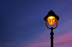 Lamppost illuminated. A lamppost illuminated at twilight stock photos