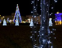 Lamppost with illumination. On the background of a New Year`s Christmas tree in the square of the city of Kherson, Ukraine, winter night stock photography