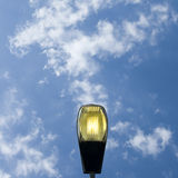 Lamppost, light on. Lamppost street light against blue sky stock images