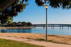Lamppost on Mission Bay in San Diego with Bridge. Lamppost at Vacation Isle Park with Mission Bay and Ingraham Street bridge in the background royalty free stock photos