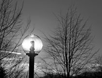 Lamppost with neon light and the sun shining Royalty Free Stock Photo