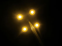 Lamppost at night with yellow golden lights. Four hands steel lamppost at night with golden light with black sky on background Royalty Free Stock Photography