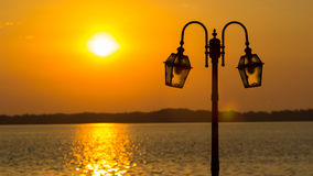 Lamppost with river and sunset Stock Images