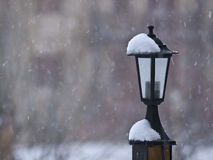 Lamppost in the Snow. Iron lamppost on a wooden post, with snow falling Royalty Free Stock Photos