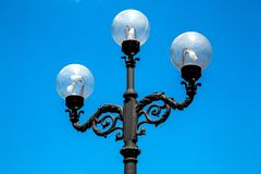 Lamppost with a triple lamp and round transparent. stock photography