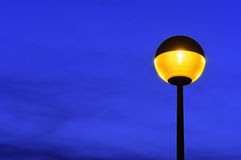 Lamppost at twilight. Lamppost illuminated at twiligh against blue sky royalty free stock photography