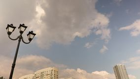 Lamppost and urban architecture. Russia, Saratov. Clouds running through blue sky. Time-lapse recording. Footage 4K, UHD.  stock video